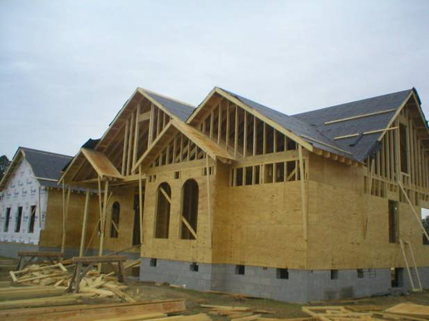 屋顶木结构承重屋架框架的外侧,已经开始铺设一层黑色的专用防水